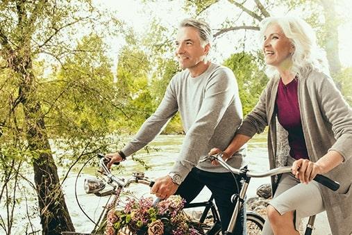 Stariji par sa slušnim pomagalima na biciklu